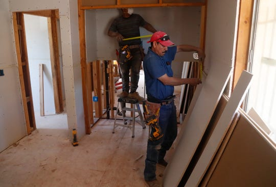 Luis Perez (left) and Luis Raul Fernandez rebuild a bedroom as Operation Enduring Gratitude renovates Gilbert Lopez's home in Glendale on May 18, 2019.