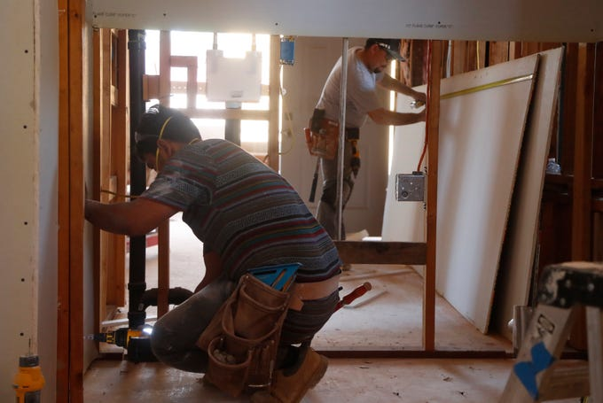 Luis Perez (left) places drywall in its spot as Operation Enduring Gratitude renovates Gilbert Lopez's home in Glendale on May 18, 2019.