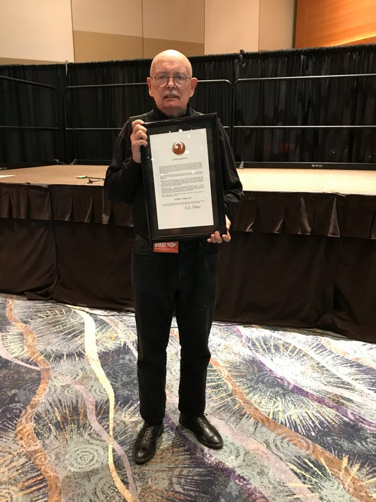 Denny O'Neil holds his proclamation declaring May 25, 2019, as Denny O'Neil Day.