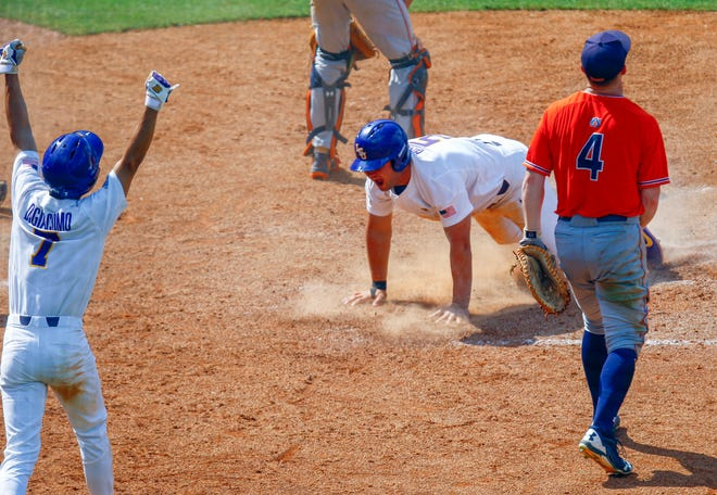 LSU's Giovanni DiGiacom (7) cheers as Drew Bianco (5) slides in safely into home on a wild pitch for the go ahead run as Auburn's Rankin Woley (4) watches during the ninth inning of the Southeastern Conference tournament NCAA college baseball game, Thursday, May 23, 2019, in Hoover, Ala. (AP Photo/Butch Dill)