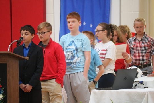 Students at Bataan Memorial Elementary School in Port Clinton take turns telling the story of the American soldiers lost during the Bataan Death March in WWII, which the school is named in honor of, as part of their annual Bataan Day ceremony.