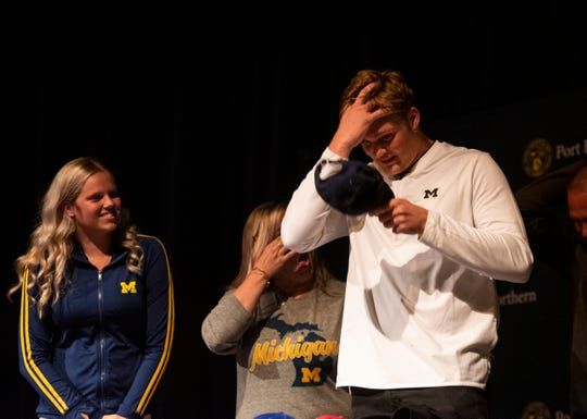 Port Huron Northern junior Braiden McGregor, right, puts on a University of Michigan hat after announcing his college decision Friday, May 24, 2019, in the auditorium at Port Huron Northern High School.