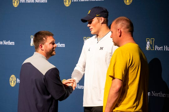After announcing his college decision, Port Huron Northern junior Braiden McGregor, center, shakes hands with Northern's head football coach Larry Roelens while his father, Steve McGregor, right, watches  Friday, May 24, 2019 in the auditorium at Port Huron Northern High School.