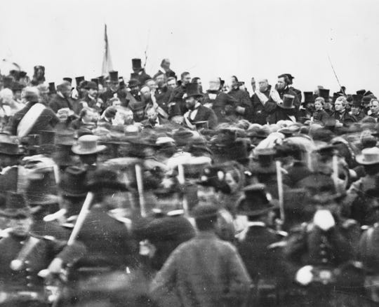 This photo shows a hatless Abraham Lincoln being greeted before giving the Gettysburg Address. The living witness to it all? The leafless branches of a honey locust tree stretching over the crowd ... just to the right of a flag pole. The tree is still alive.