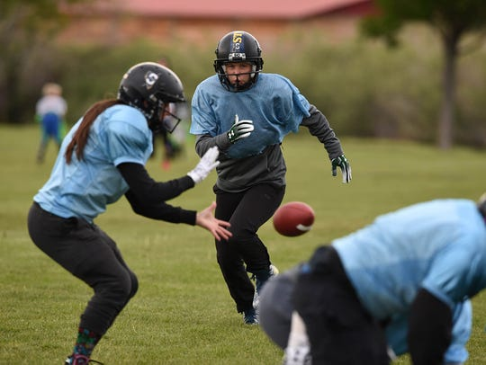 The Nevada Storm's Jesse Felker looks to get the handoff as quarterback Mo Oetjen gets the ball during practice at Mira Loma Park on May 21.