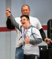 Tyler Wallace, from Oasis Academy, celebrates after receiving his medal from Rob Jacobson, Fernley Intermediate School principal.