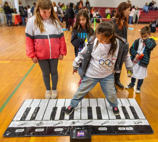 Pheonyx Mathes, 8, from Cottonwood Elementary School, plays a floor piano while her buddy, Kalyssa Aumann, 12, from Fernley Intermediate School, watches at left.