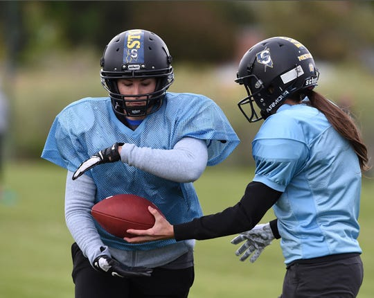 The Nevada Storm's Ashley Osborne gets a handoff from QB Mo Oetjen during practice at Mira Loma Park on May 21. The Nevada Storm is undefeated in their league.