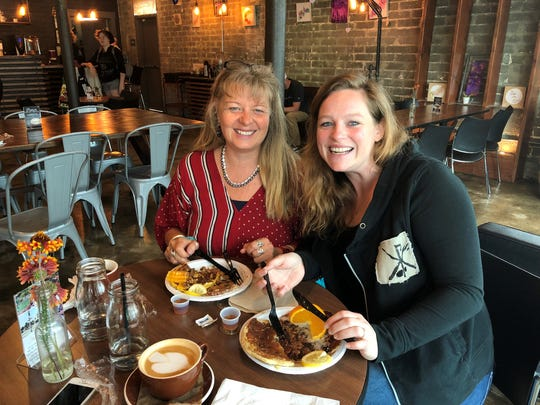Pamela Gates, left, and Tiffany Needham enjoy gourmet pancakes from the Vida pancake truck at Heritage Roasting Company in Shasta Lake City.