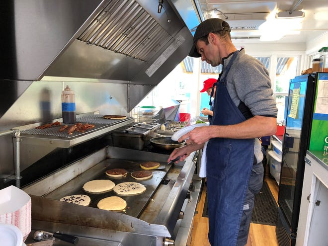 Alistair Rundle making gourmet pancakes in his Vida food truck in front of Heritage Roasting Company in Shasta Lake City.