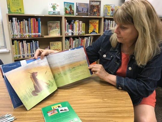 """Garfield Elementary librarian Susan Thies shows off one of the few Lakota-translated books her library has. Next year though, shelves will hold copies of """"Tatanka and Other Legends of the Lakota People,"""" the first book in the history of the Young Readers program by the South Dakota Humanities Council to be made available in both Lakota and English."""