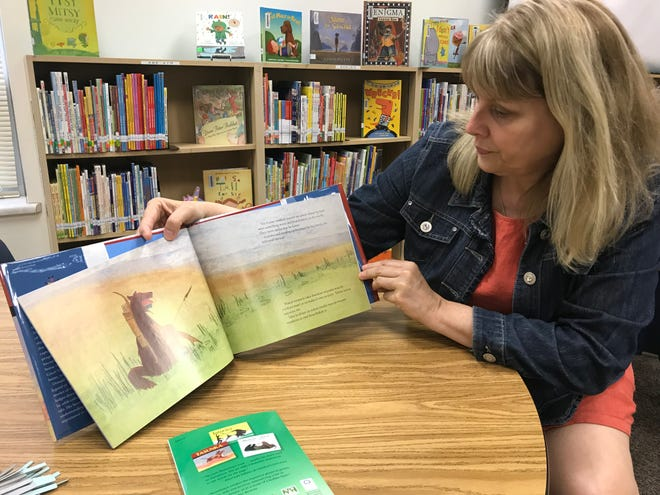 "Garfield Elementary librarian Susan Thies shows off one of the few Lakota-translated books her library has. Next year though, shelves will hold copies of ""Tatanka and Other Legends of the Lakota People,"" the first book in the history of the Young Readers program by the South Dakota Humanities Council to be made available in both Lakota and English."
