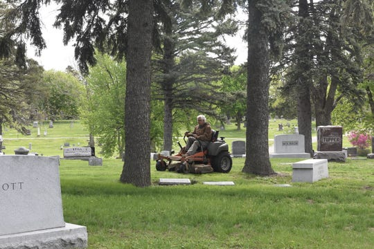 Randy Pudwill mows the grass at Mount Pleasant Cemetery on May 23, 2019 in preparation for Memorial Day.