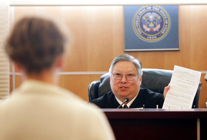 """FILE - In this May 25, 2010, file photo, Judge Michael Kwan talks with a defendant during drug court in Taylorsville, Utah. Kwan, a longtime Utah judge has been suspended without pay for six months for comments he made online and in court criticizing President Donald Trump that the state's supreme court determined violated the judicial code of conduct. The Utah Supreme Court said in a decision posted Wednesday, May 22, 2019, that Judge Michael Kwan's numerous online posts in 2016-2017 criticizing Trump diminished """"the reputation of our entire judiciary."""" (Jeffrey D. Allred/The Deseret News via AP, File)"""