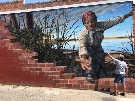 Artist MIchael Rosato, a 1983 graduate of Florida State University, applies protective coating to his mural of abolitionist Harriet Tubman in Cambridge, Maryland.
