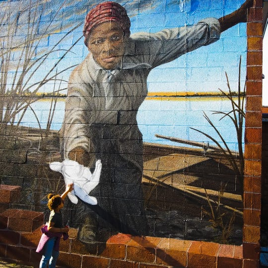 "A photo captured by Tracy Lynndee in Cambridge, Maryland of her 3-year-old granddaughter, ""Lovie"" Hope Duncan touching the hand of abolitionist Harriet Tubman has become a viral sensation on the internet."