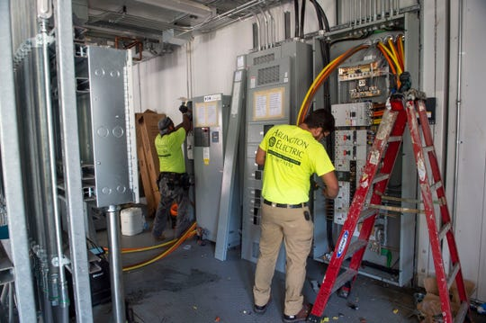"""Arlington Electric electricians John Bradley (left) and Kennethe Claus work on wiring in the new chiller plant, part of a Martin County Commission-approved improvement project to the Martin County jail and other Martin County Sheriff's Office facilities on Thursday, May 23, 2019, in Stuart. Plans include five jail pods to be renovated, a new K-9 building and kennel, a new generator and remodeled storage space. """"If I had to simplify it down, I'd say it's a mandatory face-lift for a 30-year-old correctional facility,"""" said Martin County Sheriff William Snyder."""