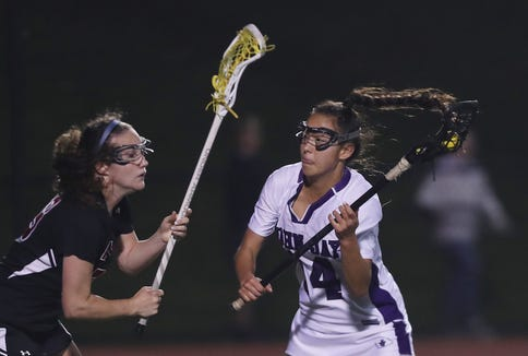 From right, John Jay's Mia DiChiara (14) drives to the goal against Rye during the girls lacrosse Section 1 Class C championship game at Fox Lane High School in Bedford May 23, 2019. John Jay won the game 8-7.