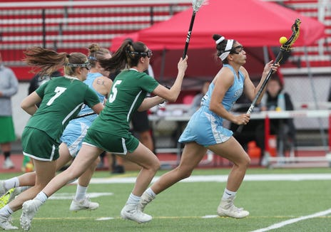 Suffern's Anna Maria Gragnani (12) controls a pass in front of Yorktown defenders during the Section 1 girls lacrosse championship game at Fox Lane High School in Bedford May 23, 2019.