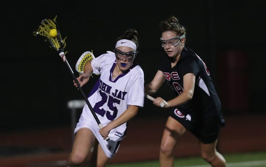 From left, John Jay's Charlotte Wilmoth (25)  drives to the goal in front of Rye's Paige Drago (28) during the girls lacrosse Section 1 Class C championship game at Fox Lane High School in Bedford May 23, 2019. John Jay won the game 8-7.