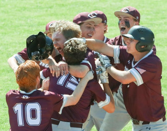 Concord mobs Steven Cornog (center, back to camera) after his seventh-inning double drove in the winning run in the Raiders' 6-5 walk-off win against A.I. du Pont in the first round of the DIAA Baseball Tournament on Friday at Concord High School.