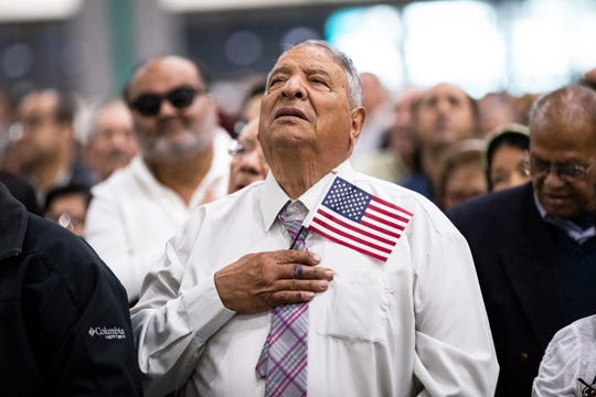 A new U.S. citizen holds an American flag as he sings the national anthem during a naturalization ceremony at a convention center in Los Angeles on May 22, 2019.