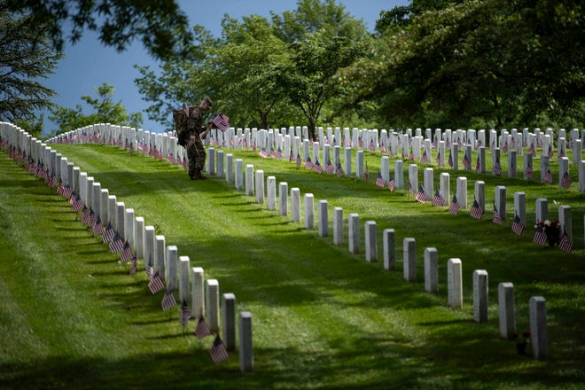 Around 1400 members of the 3rd United States Infantry Regiment, also known as The Old Guard, place flags in front of each headstone at Arlington National Cemetery on May 23, 2019.