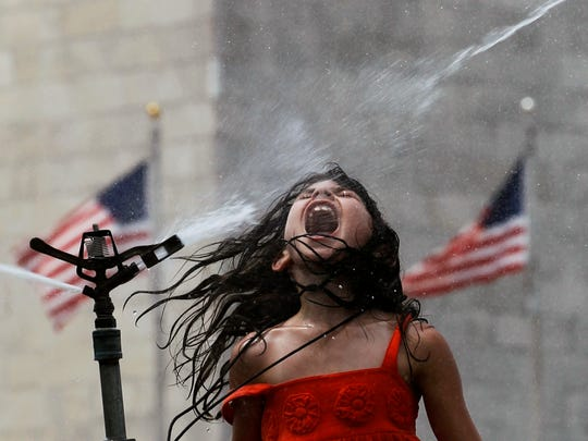 Patty Wesel, 8, from Marietta, Georgia, jumps in the spray of a sprinkler on the National Mall in front of the Washington Monument on July 7, 2010.