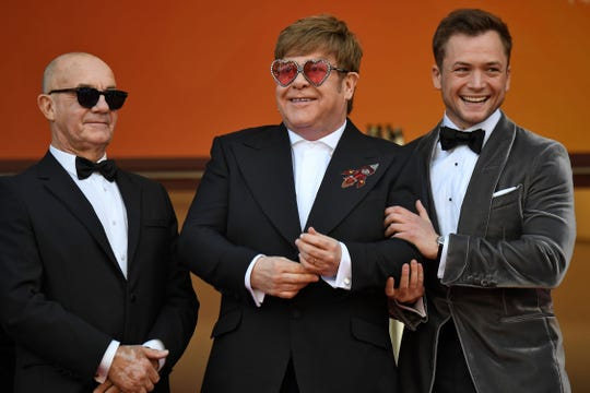 "Elton John, center, arrives for the ""Rocketman"" premiere flanked by his songwriting partner Bernie Taupin, left, and Taron Egerton, who portrays him in the biographical film."