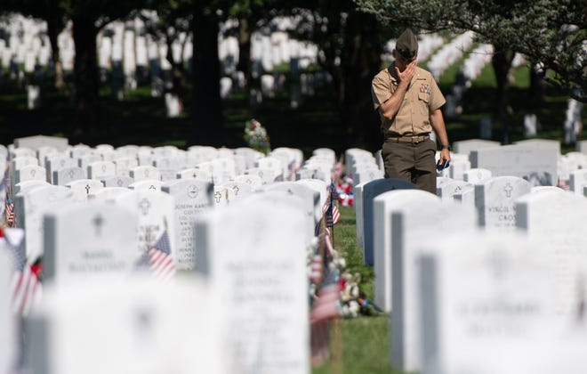 A member of the U.S. military visits Section 60 at Arlington National Cemetery on May 24, 2019, ahead of the Memorial Day weekend.