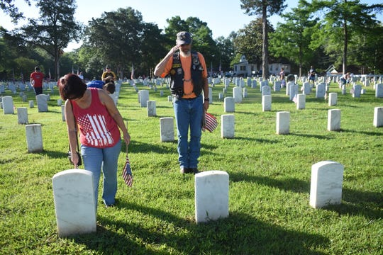 Greg Carbo (right), an Army National Guard veteran, salutes after placing a flag on one the gravesites at Alexandria National Cemetery Saturday, May 25, 2019. Also helping place flags is his wife Theresa Carbo. Volunteers place flags on the 7,816 gravesites at the Alexandria National Cemetery in preparation for the Memorial Day program set for Monday. Alexandria mayor Jeff Hall is the guest speaker. The cemetery is located at 209 East Shamrock Street in Pineville. The Memorial Day program begins at 9:45 a.m. Monday. A patriotic musical and reading, placing of wreaths by various Veteran service organizations, a rifle salute and the playing of taps are among the program activities. All Americans are asked to participate in a National Moment of Remembrance at 3 p.m. Monday to remember and honor military personnel who died in service to the U.S.