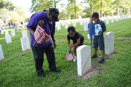 U.S. Army and Desert Storm veteran Christopher Josiah (far left) watches as granddaughter Ja'Nayah Lee places a flag at the headstone of one of the gravesites at the Alexandria National Cemetery Saturday, May 25, 2019. His grandsons Kayden Lee and Zaydin Lee also helped. are Volunteers placed flags on the 7,816 gravesites at the Alexandria National Cemetery in preparation for the Memorial Day program set for Monday. Alexandria mayor Jeff Hall is the guest speaker. The cemetery is located at 209 East Shamrock Street in Pineville. The Memorial Day program begins at 9:45 a.m. Monday. A patriotic musical and reading, placing of wreaths by various Veteran service organizations, a rifle salute and the playing of taps are among the program activities. All Americans are asked to participate in a National Moment of Remembrance at 3 p.m. Monday to remember and honor military personnel who died in service to the U.S.