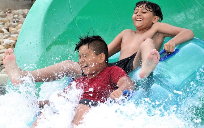 Giovanni, red shirt, and his brother Oscar hit the water at the end of a ride Saturday down the Green Monster on opening day at Adventure Cove, the city of Abilene's aquatic facility at Rose Park. The boys' family is visiting this weekend from Fort Worth.