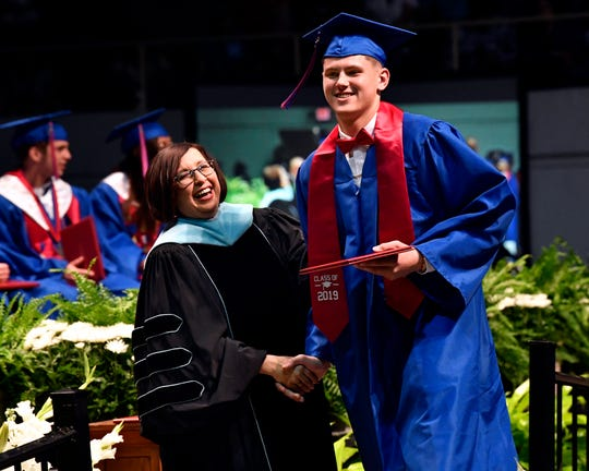 Departing Cooper High School Principal Karen Munoz laughs and claps Deven Bailey on the shoulder after giving the graduate his diploma holder during Saturday's commencement ceremonies at the Taylor County Coliseum.