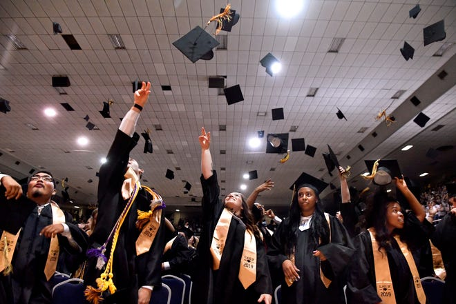 Abilene High School new alums throw their mortar board caps into the air at the end of Saturday's commencement ceremonies at the Taylor County Coliseum. AHS graduated 462 students.