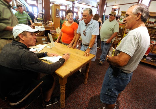 Baylor head football coach Art Briles talks with Jesse Macias (right), from Rule, and his brother Joe (right center) and sister-in-law, Ann, during a book signing on July 19, 2014, at the Texas Star Trading Company. Jesse Macias was a high school classmate of Briles at Rule High School.