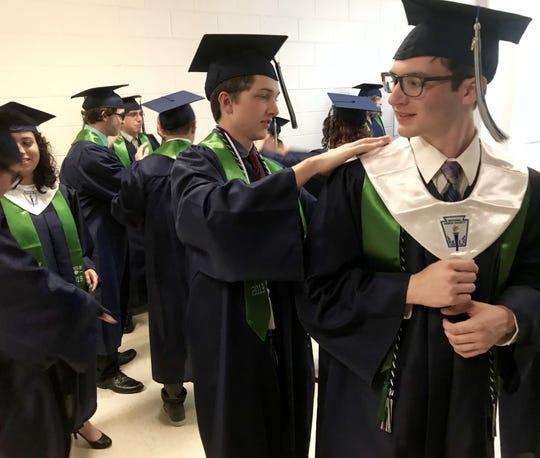 Seth Fry checks Jerold Elliott over before Saturday evening's ATEMS graduation ceremony at the Taylor County Coliseum.