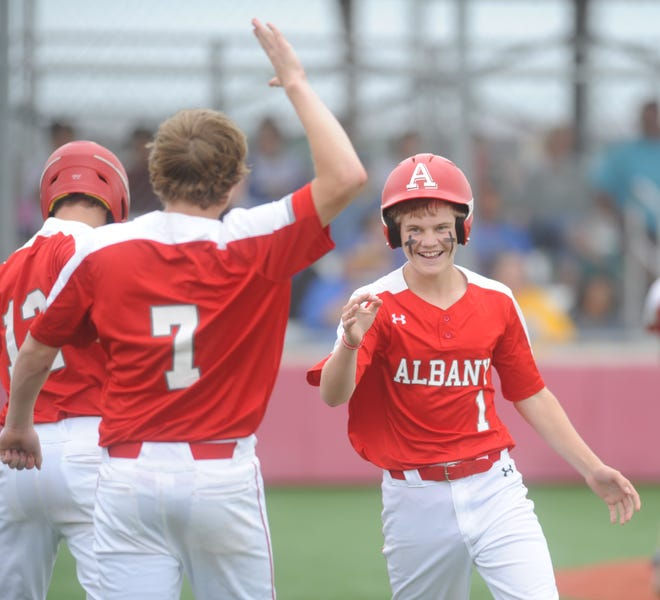 Albany right fielder Cooper Fairchild (1) goes to high-five teammate Cade Neve after scoring a run in Game 2 of a Region I-2A semifinal baseball series against Hale Center on Saturday at Hermleigh Cardinal Field.