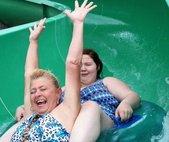 Lorrie Apple, left, screams her way down the Green Monster on Saturday at Adventure Cove. The city's aquatic facility opened for its third season.