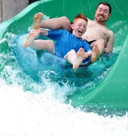Joe Max Tomlin and his son, Jace, ride it out on the Green Monster on Saturday at Adventure Cove in Rose Park. It was opening day at the aquatic facility.