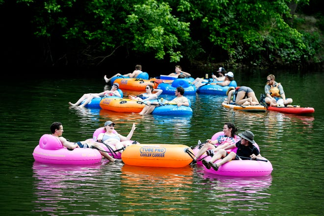 People cool off by floating down the French Broad River as temperatures reached the upper 80s May 25, 2019.