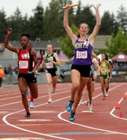 North Kitsap's Alyssa Cullen raises her arms in celebration after crossing the finish line in first place in the Class 2A girls 4x200 meter relay.