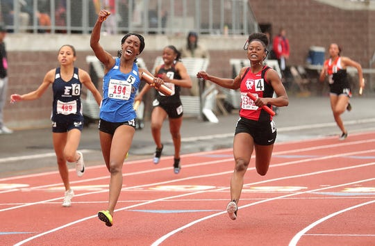 Bremerton's Tyishea McWhorter raises her fist in celebration after crossing the finish line ahead of Renton's Faith Richardson for a first-place finish in the Class 2A 4x100 meter relay during the state track and field championships at Mount Tahoma High School on Saturday, May 25, 2019.