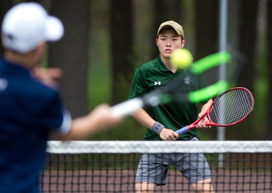 St. Johnsbury's Takahiro Matsumoto, right, readies for a return stroke from Essex's David Knickerbocker in the high school boys doubles tennis championship match at Leddy Park on Saturday, May 25, 2019.