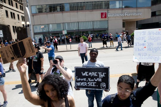 From left, Savonna Medley, Michael Lewis and Morgan Ferguson hold signs while protesting the Honorable Sacred Knights rally outside the Montgomery Courthouse Square in Dayton, Ohio, on Saturday, May 25, 2019.