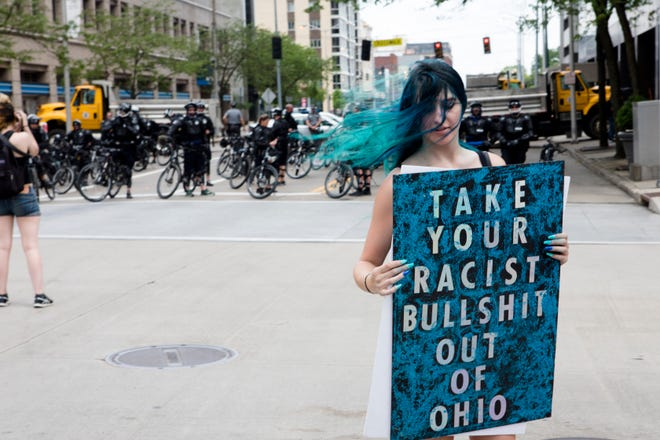 Carly Sobonya holds a sign while protesting the Honorable Sacred Knights of the Klu Klux Klan rally outside the Montgomery Courthouse Square in Dayton, Ohio, on Saturday, May 25, 2019.