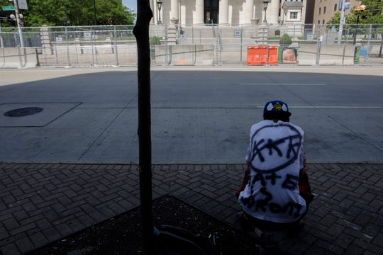 Mike Hale, of Cleveland, sits on the street while protesting the Honorable Sacred Knights rally outside the Montgomery Courthouse Square in Dayton, Ohio, on Saturday, May 25, 2019. The Honorable Sacred Knights, a Klu Klux Klan affiliated group, received permit to hold a rally from 1 p.m. until 3 p.m. in Downtown Dayton.