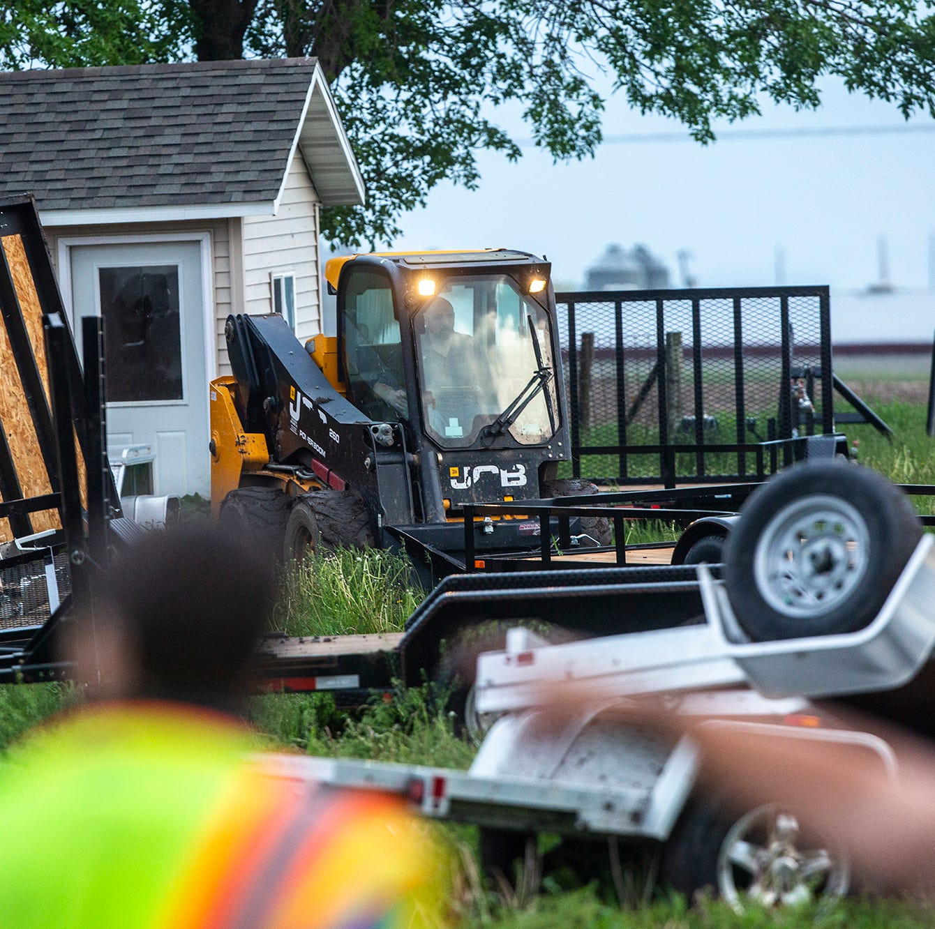 People help clean up damage to a utility trailer...