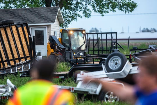People help clean up damage to a utility trailer business, Friday, May 24, 2019, in Johnson County, Iowa.