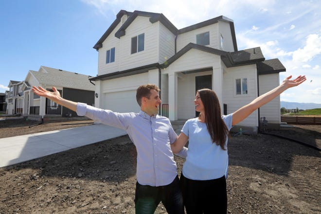 Andy and Stacie Proctor stand in front of their new home in Vineyard, Utah, on April 27. The Proctors ultimately made a successful offer on a three-bedroom house for $438,000 in Vineyard.